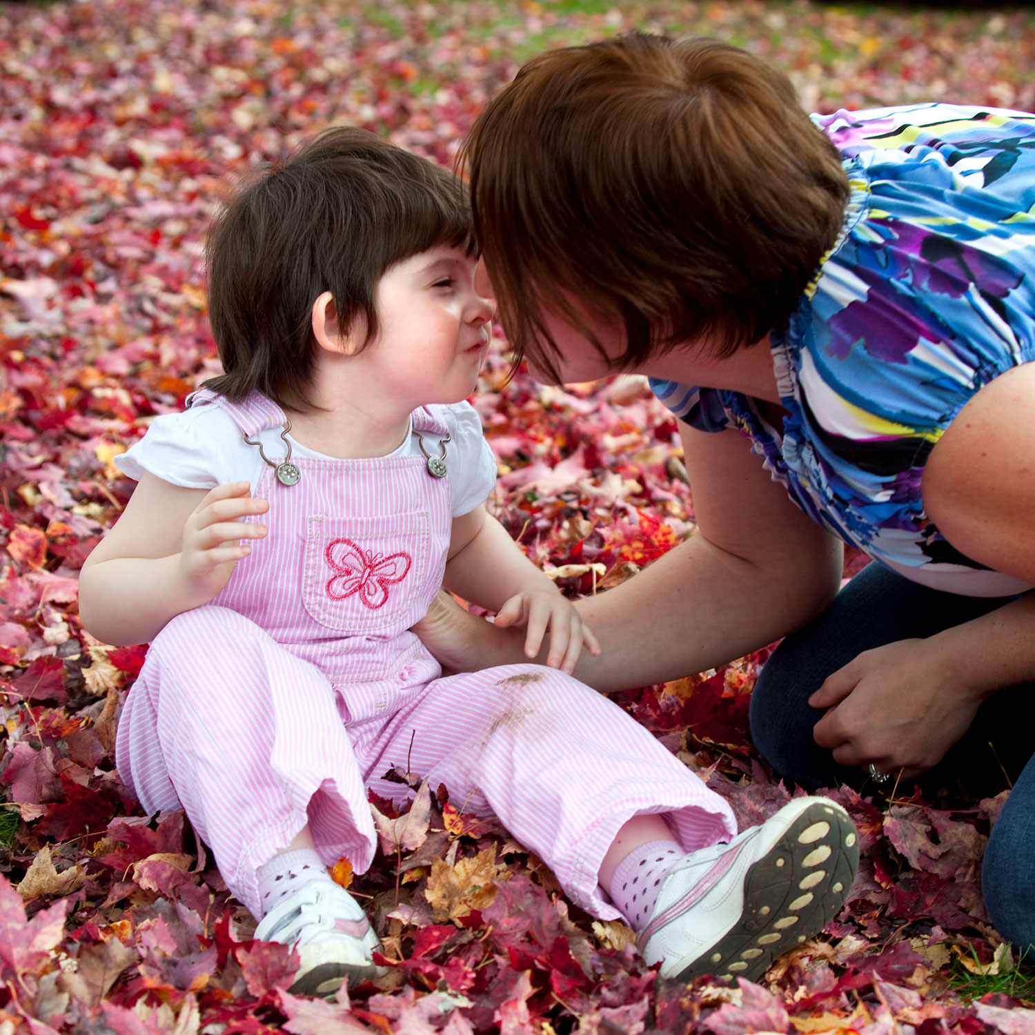 Toddler seated in autumn leaves outside. Adult kneels beside her. They give each other a kiss.